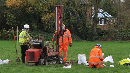 Surveyors working on the playing field with a machine to dig bore holes in the search for other grou