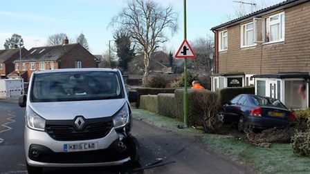 The car which ended up in a front garden after hitting a parked van (left)