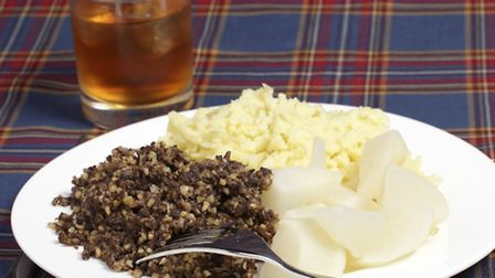 Haggis, turnips, mashed potatoes and a glass of whisky on a tartan background - the ingredients for