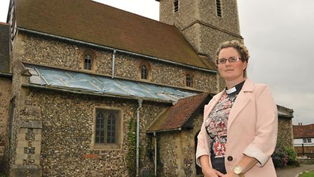 Reverend Em Coley in front of St Leonards Church where lead panels were stolen from the roof