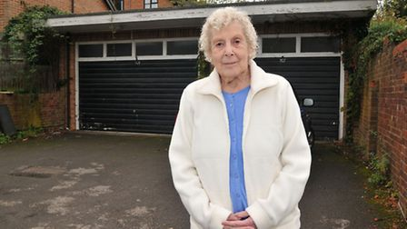 Maureen Warner in front of the garages which will be knocked down to make way for flats