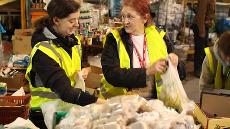 A BOB fm reporter helps to sort onions and garlic with StAR trustee Liz Needham (right)