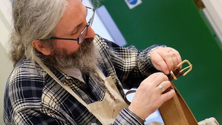 A crafter hand stitches a leather belt at the Royston Craft Fair