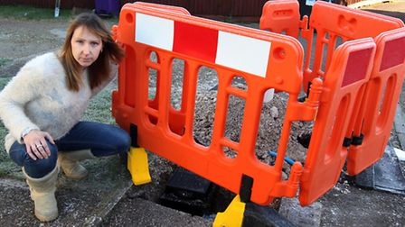 Becky Littlechild next to one of the holes left by Affinity Water, which has since been filled.