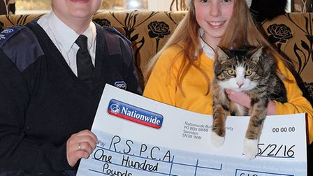 RSPCA animal collection officer Kate Wright receives a cheque from Ruby Nicholls and her cat Pippin
