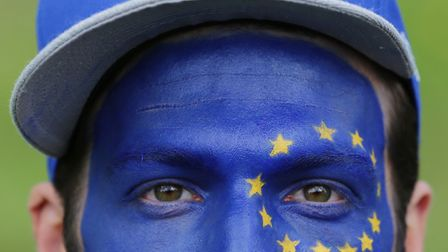 A man with the flag of the European Union painted on his face as Remain supporters gather for a prot