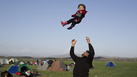 A Syrian man plays with his one-year child (AP Photo/Petros Giannakouris)