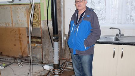 Ian Tassell next to where his bathroom was and the leaking soil stack in his apartment