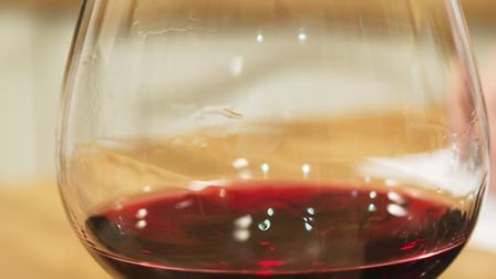 Glass of red wine on kitchen counter.