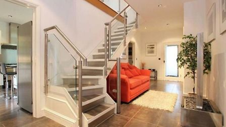 The hallway has recessed halogen spotlights, tiled flooring, contemporary staircase with glass and s