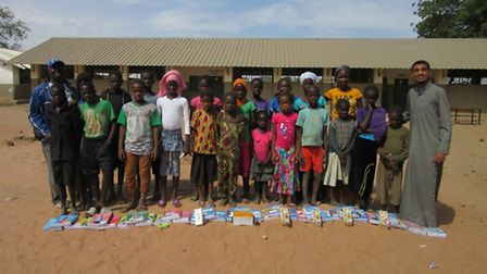 Khaled Hassan: Handing out exercise books and stationery to students at a Gambian school