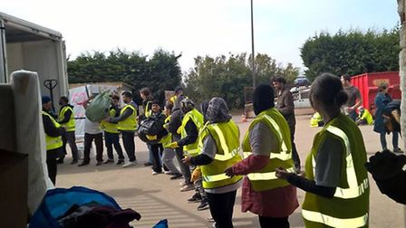 Volunteers from StAR line up to distribute donatiosn to the donation warehouse in Calais