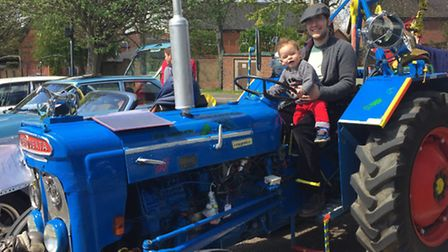 Thomas Asher, 1, has a go at the wheel of a Fordson Super Dexta tractor from the 1960s, helped by da