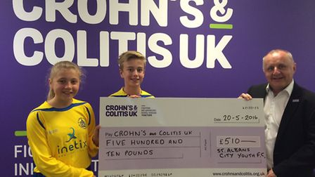 St Albans City Youth players Sam Tillin and Jasmine Price present the cheque to David Barker of Croh