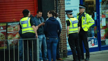 St Albans police officers, in Hatfield Road, before executing a warrant at a Londis convenience stor