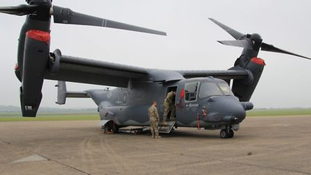 Members of the crew of the vertical lift off American Air Force V 22 inspect their plane before take