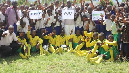 Deo Okello (centre) and pupils saying thank you for ball and kit donations
