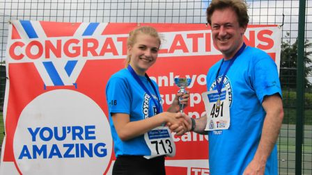 Thomas Kelly of Margaret House presenting Sophie Pedder, winner of the junior female section, with h