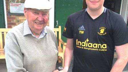Ramsey bowler Tim Willis receives his man-of-the-match award from Huntingdonshire cricketing legend