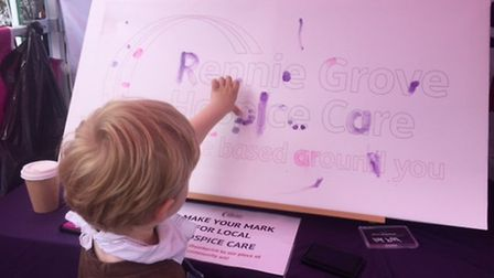 A little boy finger-painting on the Rennie Grove logo