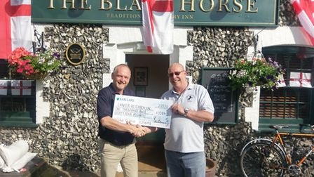 Keith Barrell receiving a cheque from Steve Harrington of The Black Horse pub.