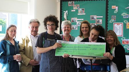 Staff and students from Spring Common Academy present their cheque to EACH.