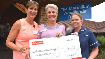 Gwen King (centre) hands over a cheque for £1000 from her card sales, At the Woodlands Centre to (le