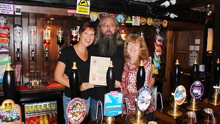 Juliet Ferris, Huntingdonshire CAMRA's social secretary (left), presenting the award to licensees Pa