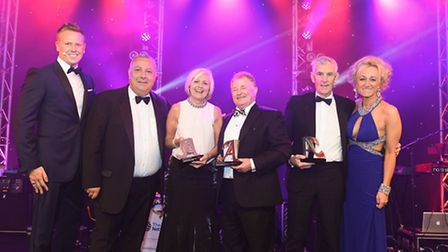 Renford Sargent, chairman of Premier Travel (centre) receiving his award at the Travel Weekly Agent
