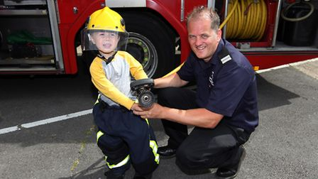 Evan Mudge gets to grips with the special firefighter equipment, helped by crew commander Derek Hult