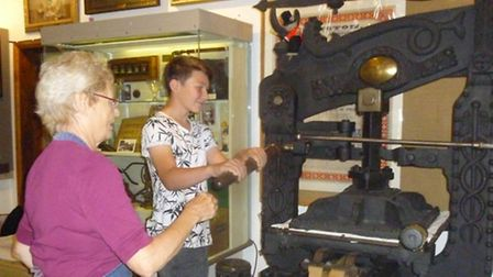 Liz Beardwell, print workshop leader, and a member of the public having a go using the Crow printing