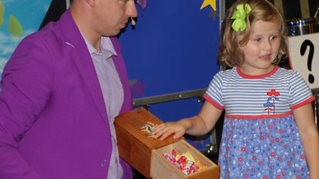 Three-year-old Maddie Denison from Tewin near Welwyn Garden City with Mr. Bean the conjuror, and the
