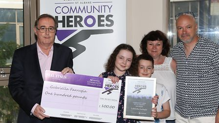 Maltings centre manager Phil Corrigan presents Gabriella Farrugia and her family with her award and