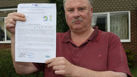 Charles Hazlewood holding a fraudulent letter stating he had won £900,000 in the International FIFA