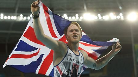 Jonnie Peacock holds the Great British flag aloft after defending his T44 100m Paralympic title. Pho