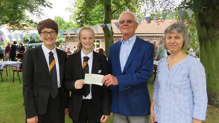 Bassingbourn Village College students Eden Alarcon, Tyra Jones present the cheque to Edward Sage & K