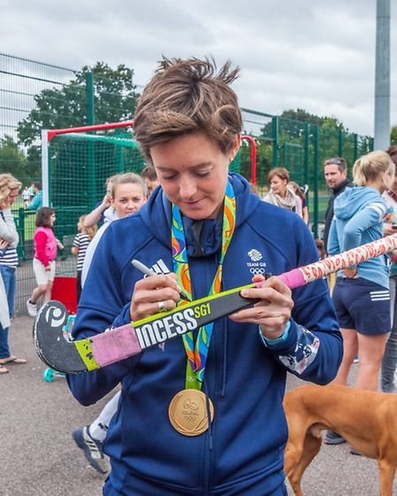 Rio 2016 Olympic gold medalist Hannah Macleod shows off her gold medal with the delighted members of