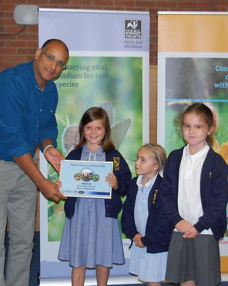 Zephaniah presenting certificate to How Wood School, the runners up in the Vibrant Vegetables catego