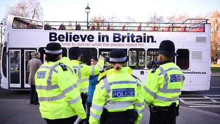 Metropolitan Police officers at Parliament Square in London as the Vote Leave bus passes by. Photogr