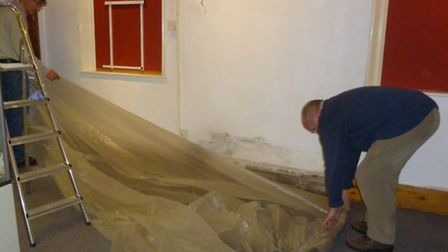 Volunteers laying plastic sheeting to protect the floor at Royston's museum.