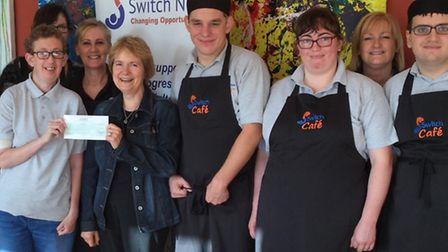 Christine Shaw handing over the cheque to the Switch Now Cafe.