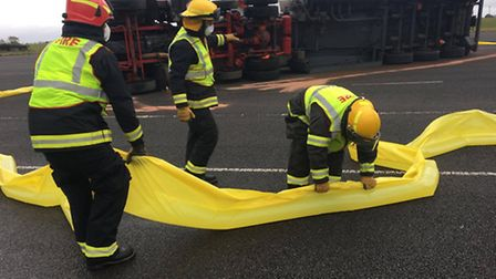 Crews lay out the water-filled barrier to contain the spill.