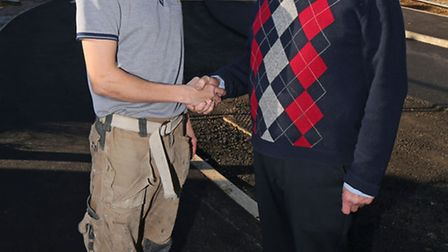 Ben Bagshaw (left) shakes hands with neighbour David Walker after waking him at 1am to alert him to