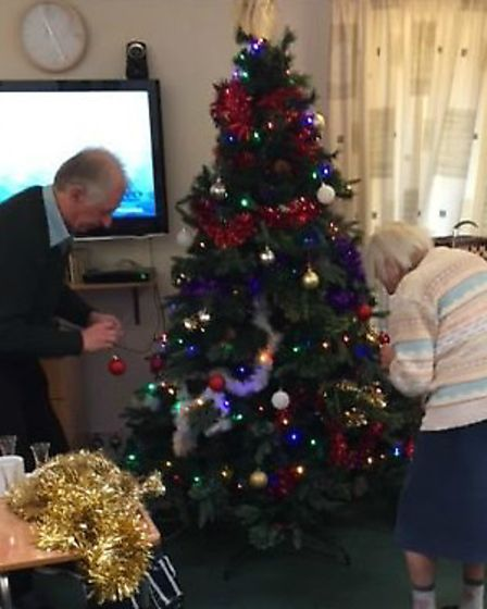 Royston Rotarians putting up a Christmas tree with residents at Richard Cox House.