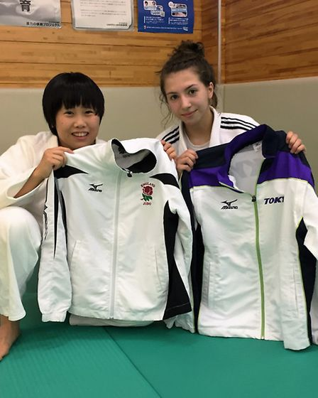 Amy Platten and a Japanese athlete swap tracksuits