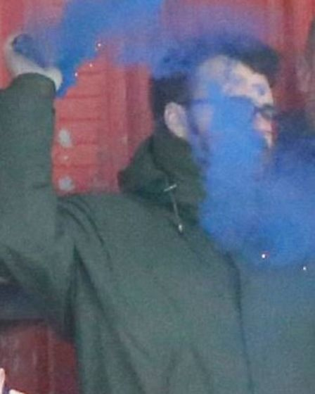 The Saints supporter was captured with the smoke bomb during the match with Hemel Hempstead Town FC