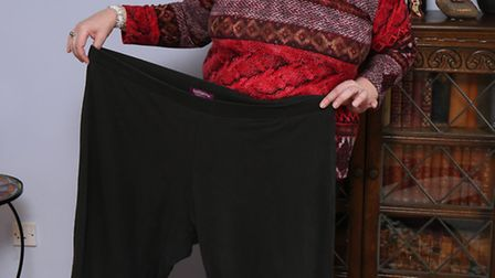 Maxine Crawley, who has lost 8 stone in about a year, with an old pair of her trousers.