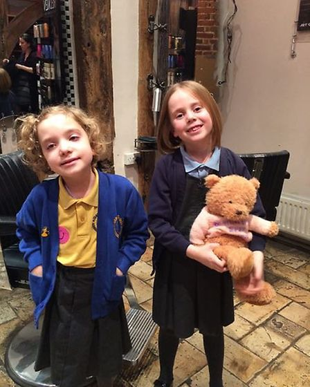 Lyla Cohen, 6, and Bessie Davis, 7, at Artisan Hairdressers in St Albans, posing with Bessie Bear. L