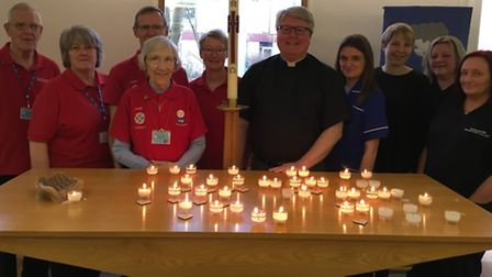 The Rev Scott Watts with volunteers and staff at the service of remembrance