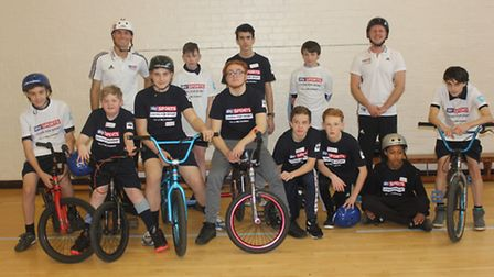 A group of students with BMX world champion Mike Mullen (left) and wheelchair rugby Paralympian Aaro